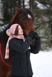 Beautiful teenager girl hugging brown horse in winter Stock Photography