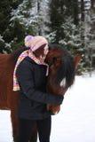 Beautiful teenager girl hugging brown horse in winter Stock Photo