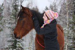 Beautiful teenager girl hugging brown horse in winter Stock Photo