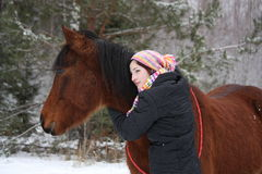 Beautiful teenager girl hugging brown horse in winter Royalty Free Stock Image