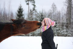 Beautiful teenager girl playfully kissing brown horse in winter Royalty Free Stock Image