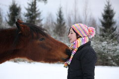 Beautiful teenager girl playfully kissing brown horse in winter Stock Image