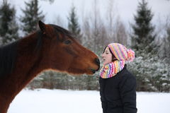 Beautiful teenager girl playfully kissing brown horse in winter Stock Photos