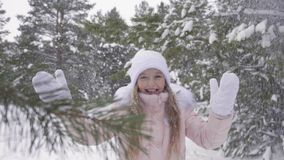 Beautiful teenager girl rejoicing winter snowfall in snowy forest slow motion stock video