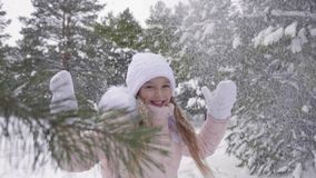 Beautiful teenager girl rejoicing winter snowfall in snowy forest slow motion. Happy young girl enjoying snowfall while walking in winter forest at frosty day royalty free stock images
