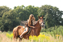 Beautiful teenager girl riding horse at the field of flowers Royalty Free Stock Photography