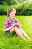 Beautiful teenager girl sitting on grass with digital tablet Stock Photography