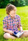 Beautiful teenager girl sitting on the grass and reading book. Vertical portrait Stock Photography