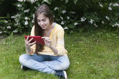 Beautiful teenager girl with tablet computer sits on the grass in Park. Photo Royalty Free Stock Photography