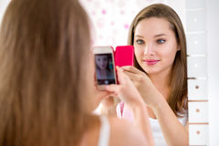 Beautiful teenager girl taking selfie in bathroom Stock Image
