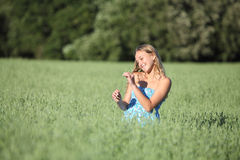 Beautiful teenager girl touching a oat stem Royalty Free Stock Photos