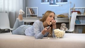 Beautiful teenager girl watching tv and eating pop corn, entertainment time. Stock photo royalty free stock photos