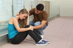 Beautiful teenager girl worried and a boy comforting her. Beautiful teenager girl worried sitting on the floor and a boy comforting her Stock Photography
