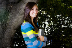 Beautiful Teenager holding a Book. With Leaves in the Background Royalty Free Stock Photo
