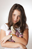 Beautiful teenager holding a doll in her arms Stock Photo