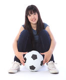 Beautiful teenager Japanese soccer student girl. Portrait of a beautiful young Japanese teenager high school student girl sitting on the floor with soccer ball Royalty Free Stock Photos