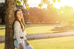 Beautiful teenager leaning on a tree Stock Image
