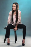 Beautiful teenager sitting on a stool Stock Photo