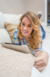 Beautiful teenager using tablet pc liying on sofa Stock Image