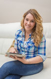 Beautiful teenager using tablet pc sitting on sofa Royalty Free Stock Photography