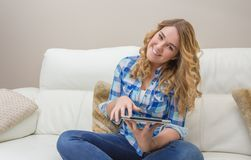 Beautiful teenager using tablet pc sitting on sofa Royalty Free Stock Images