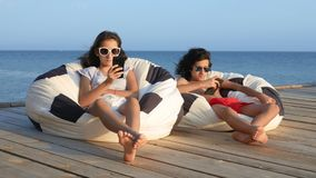 Beautiful teenagers boy and girl sitting in a bag chair on a wooden terrace over the sea. They talk joyfully. concept of stock video