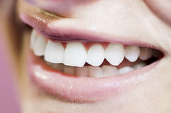 Beautiful teeth smile. Beautiful womans smile on pink background Royalty Free Stock Photography