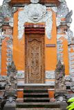 Beautiful temple wood and stone decorative gate with traditional asian patterns and sculptures. In Bali, Indonesia stock image