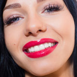 Beautiful tempting brunette young woman with blue eyes, long lashes, red lipstick, happy smiling & looking at camera closeup Royalty Free Stock Photography