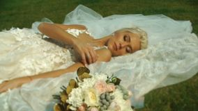 Beautiful tender blond bride in wedding dress is lying on the grass near the wedding bouquet. Beautiful tender blond bride in wedding dress is lying on the stock video footage