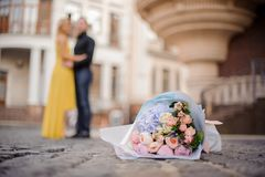 Beautiful and tender bouquet of flowers on the cobbled road. Against the blurred background of hugging couple Royalty Free Stock Photo