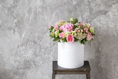 Beautiful tender bouquet of flowers in white box on gray ackground with space for text. Assembled a bouquet of professional florists. gentle colors royalty free stock photos