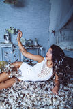Beautiful tender girl in feathers room Stock Images
