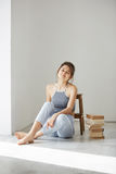 Beautiful tender girl smiling looking at camera sitting on floor with books over white wall. Stock Photos