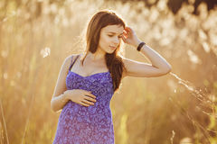 Beautiful tender pregnant woman smiles and enjoys a sunny summer Stock Image