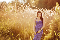 Beautiful tender pregnant woman smiles and enjoys a sunny summer Royalty Free Stock Photos
