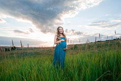 Beautiful tender pregnant woman standing on green grass Stock Photo