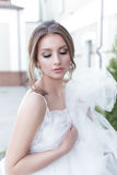 Beautiful tender sweet girl bride with a festive hairdo and light make-up with a veil in her hands with rich costume jewelery earr. Beautiful tender sweet girl Royalty Free Stock Photo
