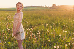 Beautiful tender sweet girl in a white lace dress with a scythe on his head standing barefoot in a field of dandelions in the sun royalty free stock photo