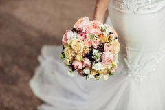 Beautiful tender wedding bouquet of roses and eustoma flowers in hands stock photos