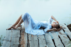 Beautiful  tender woman lying on the jetty and bored. Royalty Free Stock Images