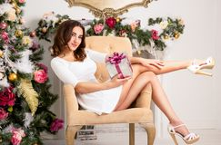 Beautiful tender young lady in chair near Christmas tree holding  gift box. Sexy woman with beautiful shapely legs Stock Photography