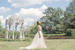 Beautiful tender young woman bride in her wedding dress gentle air walks in the lush garden on a hot sunny summer day Royalty Free Stock Photography