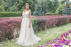 Beautiful tender young woman bride in her wedding dress gentle air walks in the lush garden on a hot sunny summer day stock photography