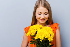 Beautiful tenderness. Beautiful young woman in pretty dress holding bouquet of flowers while standing against grey background Royalty Free Stock Images