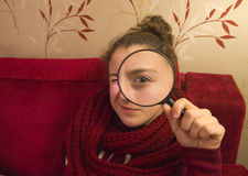 Beautiful tennager girl looking through a magnifying glass Royalty Free Stock Photo