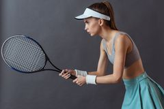 Beautiful tennis player. Beautiful girl in sportswear is holding a tennis racket, on gray background royalty free stock photo