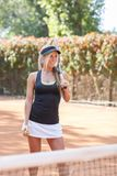 Beautiful tennis player, stands on a tennis court. Beautiful tennis player, stands on a tennis court with a racket. The concept of sport Royalty Free Stock Photography