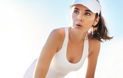 Beautiful tennis player taking a breathe. Beautiful sporty woman bending over and taking a breathe. Female tennis player taking at rest during the match Royalty Free Stock Photography
