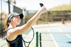 Beautiful tennis player taking selfie. Attractive female latin tennis player with racket making selfie on her smartphone on court Royalty Free Stock Images